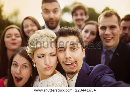 Young couple of newlyweds with group of their firends taking selfie and making funny grimaces - stock photo