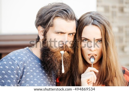 young couple of pretty girl with long hair and handsome bearded man hipster with beard holding metallized tea spoon outdoor