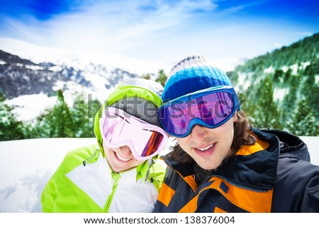 Young couple of skiers with mountains on background - stock photo