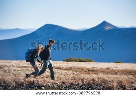 Young couple of tourists enjoying their trip in the mountains. Side view with big beautiful mountains on the background. Travelers holding hands. - stock photo