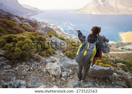 Young couple of tourists looking down at coast, man pointing at something