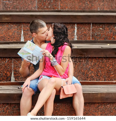 Young couple of tourists sitting on steps, kissing.