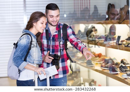 Young couple of tourists with ruchsacks on their backs are choosing new shoes from a showcase in a shopping mall - stock photo