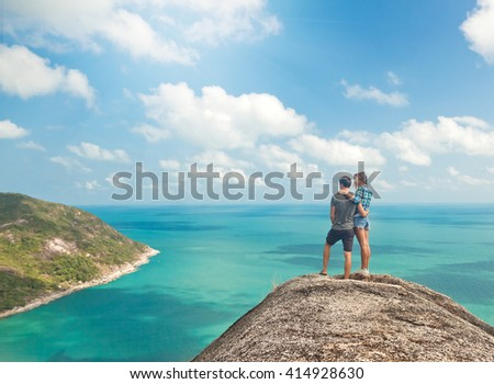 Young couple of travelers on a hill with stunning views of the ocean - stock photo