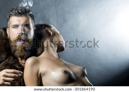 Young couple of undressed girl standing near unshaven man with beard and moustache smoking cigarette in fur coat on grey background copyspace, horizontal picture - stock photo