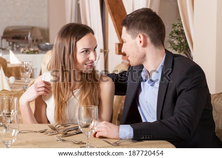 Young couple on a date flirting in restaurant - stock photo