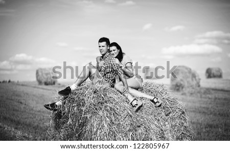 Young couple on a haystack in a field. Love stoty.