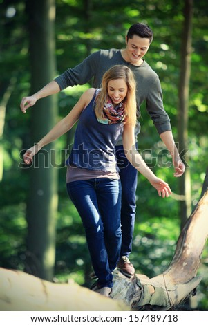 young couple on a romantic date in the forest balancing over a tree trunk - stock photo