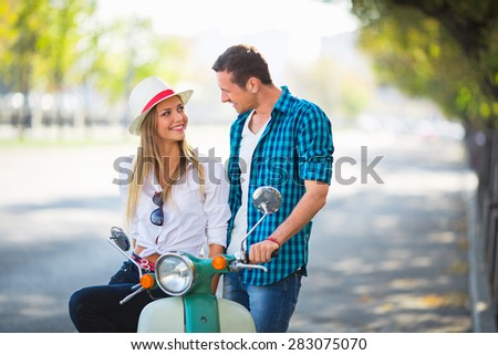 Young couple on a scooter outdoors - stock photo