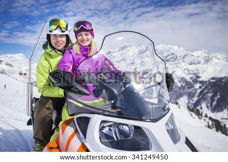 Young couple on a snowmobile ski resort - stock photo