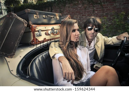 young couple on a vintage car - stock photo