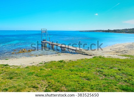 young couple on a wooden pier in Sardinia, Italy - stock photo