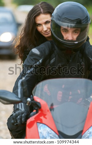 Young couple on beautiful bike on road. - stock photo