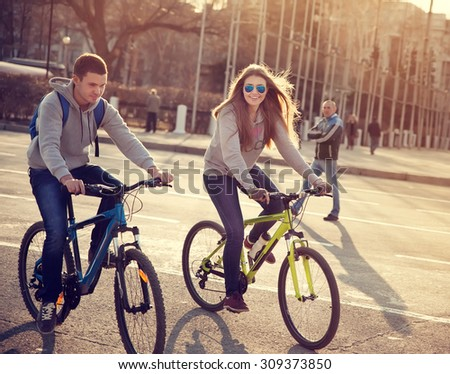 young couple on bicycles in the city at sunset - stock photo