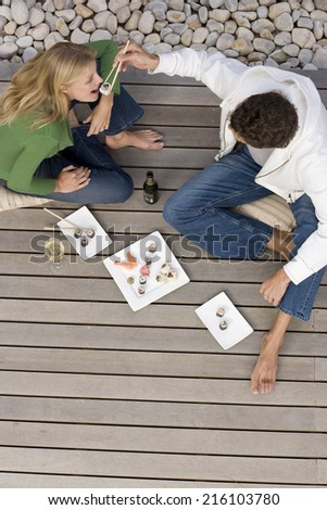 Young couple on decking, man feeding woman sushi with chopsticks, elevated view - stock photo