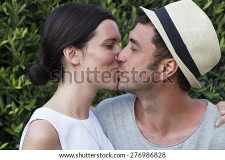 Young couple on holidays, casual, kissing each other - stock photo