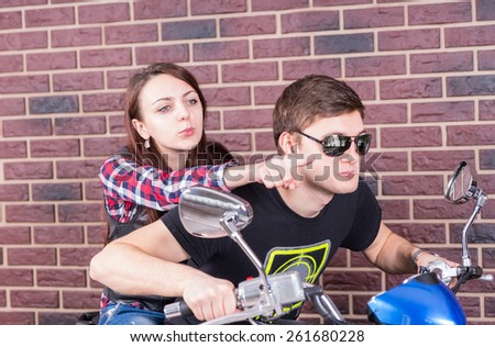 Young Couple on Motorcycle in front of Brick Wall with Woman Pointing Forward Over Mans Shoulder - stock photo