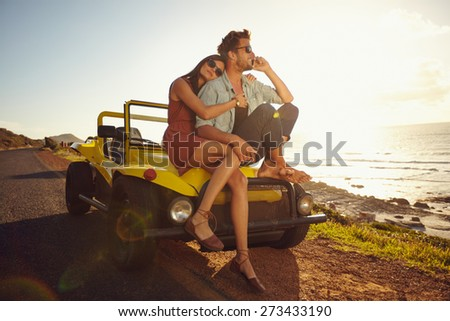 Young couple on road trip. Young couple sitting on the hood of their car with man answering a phone call and woman sitting by. Car is parked alongside coastal seashore with bright sunlight.