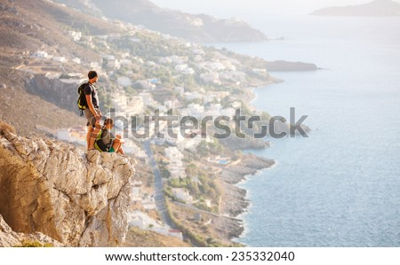 Young couple on rock and enjoying beautiful view. Kalymnos Island, Greece.  - stock photo