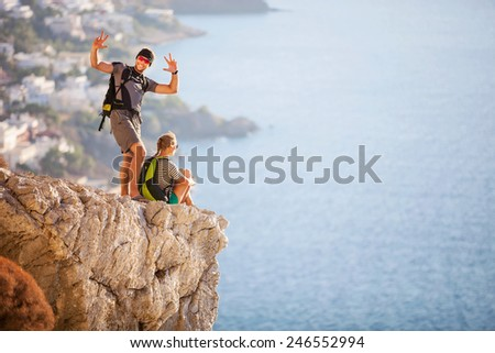 Young couple on rock and enjoying beautiful view, woman sitting on edge, guy posing and making faces - stock photo