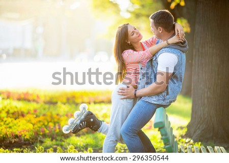 Young couple on roller skates outdoors - stock photo