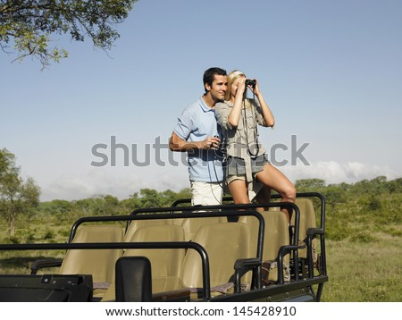 Young couple on safari standing in jeep and looking through binoculars - stock photo