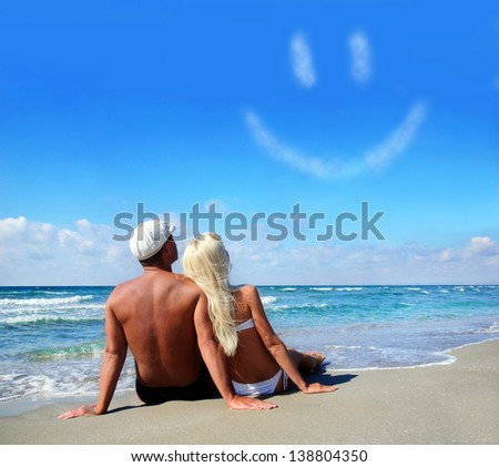 young couple on sea sand beach dreaming about the own child or about happy