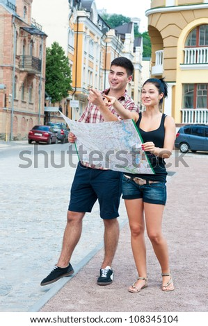 Young couple on street with a map show direction of arms. - stock photo