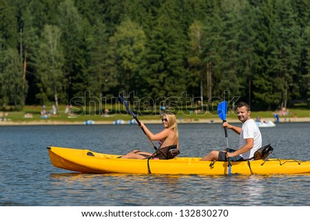 Young couple on summer weekend kayaking on pond - stock photo