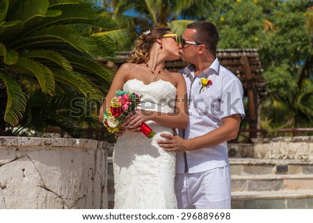 Young couple on the background of palm trees. - stock photo
