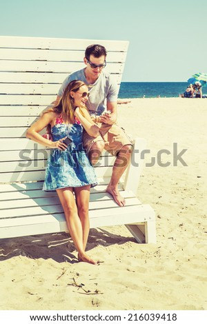 Young couple on the beach. Wearing glasses, barefoot, dressing in summer outfits, girl and guy relying on each other on a wooden structure, reading messages on mobile phones.  - stock photo