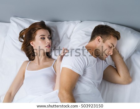 Young couple on the bed in bedroom. Caucasian models - in love, relationship, dating, happy people, bedtime concept shot.