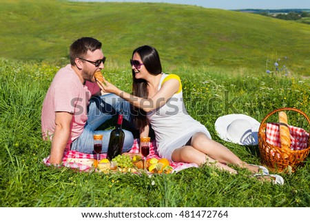 Young couple on the picnic, woman is feeding her husband