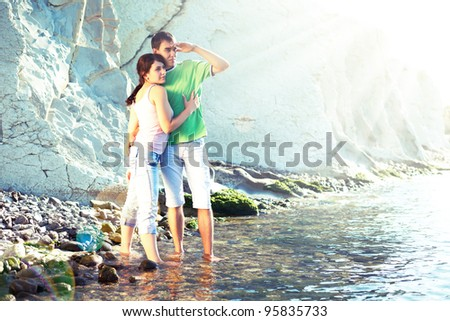 Young couple on the rocky coast standing ankle-deep in water and looking over the horizon