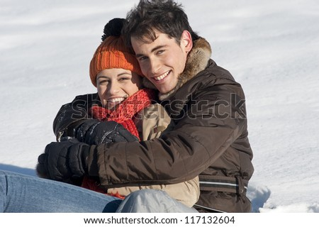 Young couple on the snow with Christmas gift