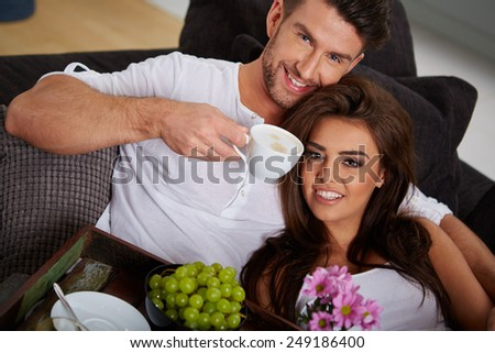 Young couple on the sofa in having fun - stock photo