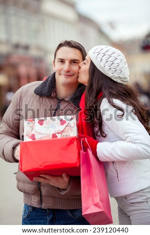 Young couple on the street carrying gift boxes and bags - stock photo