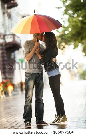 Young couple on the street of the city with umbrella - stock photo