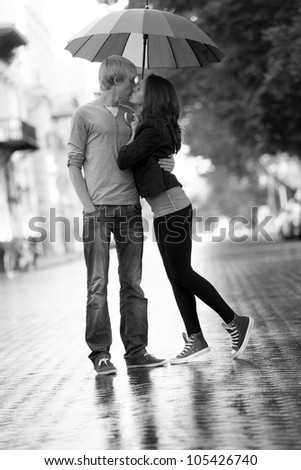 Young couple on the street of the city with umbrella. Photo in black and white style. - stock photo