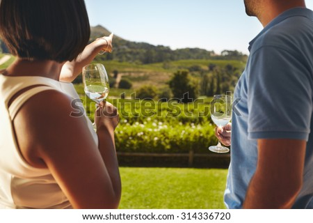 Young couple on vacation holding a glass of wine, with woman pointing away at vineyard, showing something to her boyfriend. - stock photo