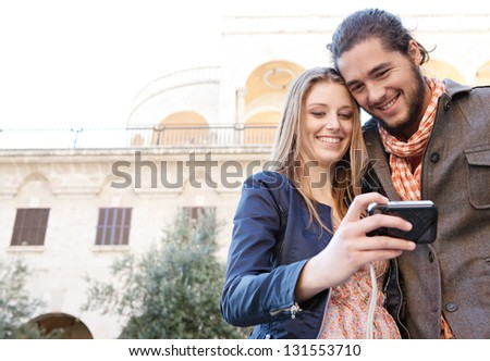 Young couple on vacation using a digital photo camera to take pictures of themselves in a destination city. - stock photo