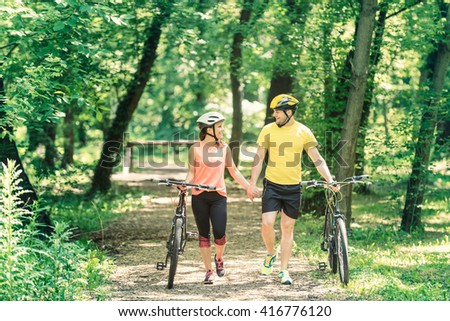 Young couple on weekend holiday, holding hands and walking with bicycles, enjoying nature