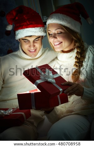 Young couple opening a glowing gift box in the dark