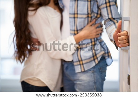 Young couple opening the door to their new home - stock photo