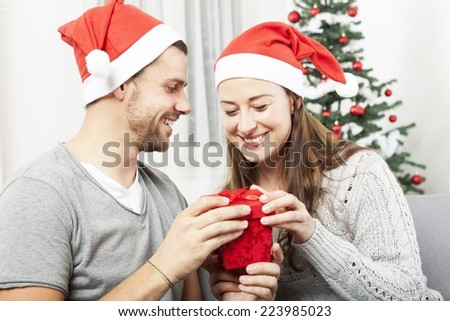 young couple opens christmas gift box and is happy in front of christmas tree
