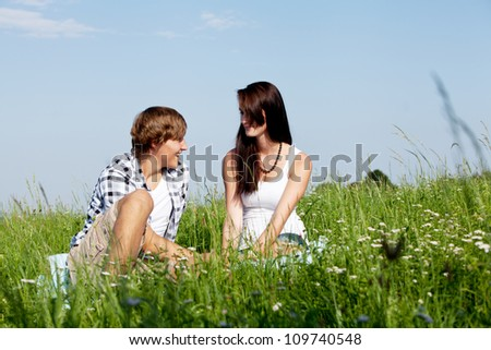 young couple outdoor in summer on blanket in love