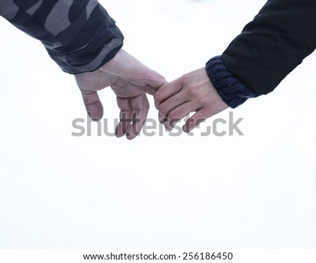 Young couple outdoors, holding hands in a winter park. Touching hands of a young couple.