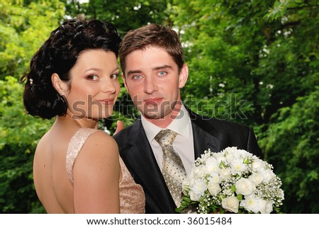 Young couple outdoors. Woman with bunch of flowers - stock photo