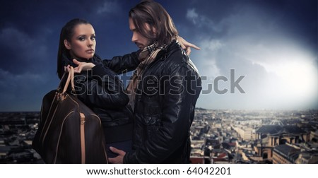 Young couple over the city background - stock photo