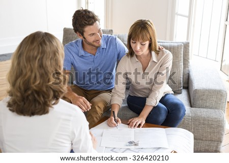 Young couple owners meeting real estate agent for house investment. Signing a contract